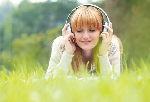 Beautiful young woman with headphones. Enjoy music outdoors. Girl repose or lie down