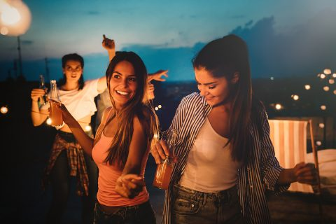 Friends enjoying cocktails at a party. Group of people having fun, dancing on a rooftop