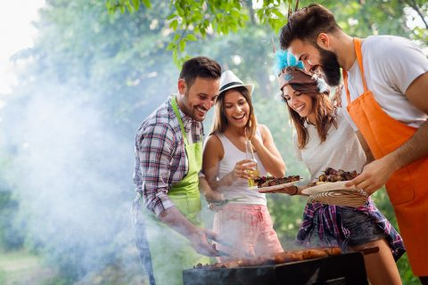 Happy friends making barbecue and having lunch in the nature