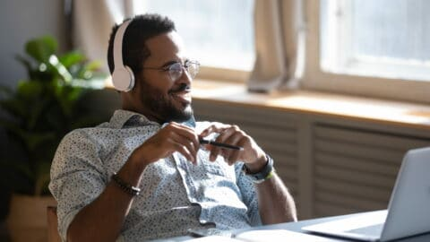 Distracted from job study happy millennial african american man in glasses listening to favorite audio music, looking away, thinking of future, enjoying pause break time alone at workplace home.